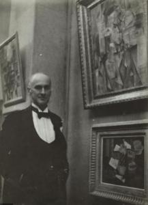 Wilhelm Uhde posant devant son portrait exécuté par Picasso en 1910